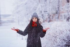 Winter girl in red gloves and scarf blowing snow. Beauty Joyful Teenage Model Girl having fun in winter park. Beautiful girl laugh Stock Photo