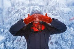 Winter girl in red gloves and scarf blowing snow. Beauty Joyful Teenage Model Girl having fun in winter park. Beautiful girl laugh Stock Photography