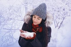Winter girl in red gloves and scarf blowing snow. Beauty Joyful Teenage Model Girl having fun in winter park. Beautiful girl laugh Royalty Free Stock Image