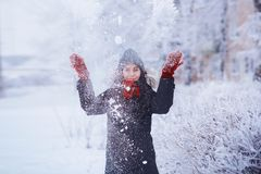 Winter girl in red gloves and scarf blowing snow. Beauty Joyful Teenage Model Girl having fun in winter park. Beautiful girl laugh Stock Image