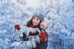 Winter girl in red gloves and scarf blowing snow. Beauty Joyful Teenage Model Girl having fun in winter park. Beautiful girl laugh Royalty Free Stock Images