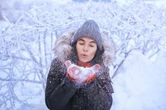 Winter girl in red gloves and scarf blowing snow. Beauty Joyful Teenage Model Girl having fun in winter park. Beautiful girl laugh Royalty Free Stock Photography