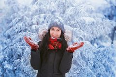 Winter girl in red gloves and scarf blowing snow. Beauty Joyful Teenage Model Girl having fun in winter park. Beautiful girl laugh. Winter girl in red gloves and Royalty Free Stock Image