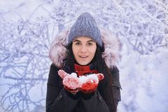 Winter girl in red gloves and scarf blowing snow. Beauty Joyful Teenage Model Girl having fun in winter park. Beautiful girl laugh Stock Images