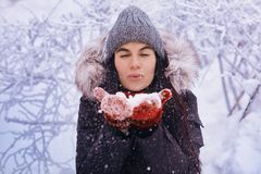 Winter girl in red gloves and scarf blowing snow. Beauty Joyful Teenage Model Girl having fun in winter park. Beautiful girl laugh. Winter girl in red gloves and Royalty Free Stock Photos