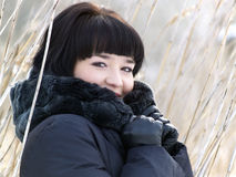 Winter girl in reed outdoors Stock Image