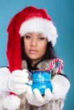 Winter girl santa helper hat holds blue mug Royalty Free Stock Image
