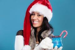 Winter girl santa helper hat holds blue mug Stock Images