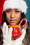 Winter girl santa helper hat holds red mug Stock Photos
