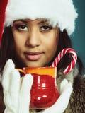 Winter girl santa helper hat holds red mug Royalty Free Stock Photo