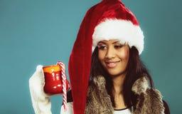 Winter girl santa helper hat holds red mug Stock Image