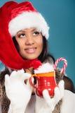 Winter girl santa helper hat holds red mug Stock Photo