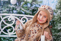 Winter. Girl sitting on the bench, smiling, rings the bell Royalty Free Stock Image