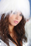 Winter girl wearing white fur hat. Winter Girl with beautiful white fur, silver dress . blue background Royalty Free Stock Photography