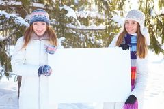 Winter. Girls with blank banner. Stock Photos