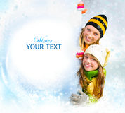 Winter Girls.Snow. Winter teenage Girls peeking from behind blank sign billboard. Space for Your Text. Sale Stock Photo