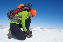 Winter glacier trekking. Young woman putting on her crampons Royalty Free Stock Photography