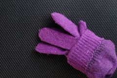 Winter glove put on dark background scene. Stock Image