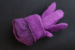 Winter glove put on dark background scene. Royalty Free Stock Images