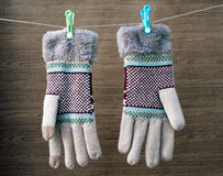 earth tone winter gloves with green and blue clothes pin hanging on white clothes line rope with dark brown wooden background stock photos
