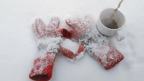 Winter gloves make the shape of a heart on a snow with a cup of hot coffee. Slow motion video. stock video footage