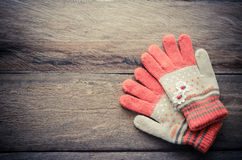 Winter gloves orange color on wooden background - tone vintage. royalty free stock photography