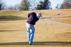 Winter Golf. Man teeing off on a par three on a winter afternoon on a public golf course Stock Photo