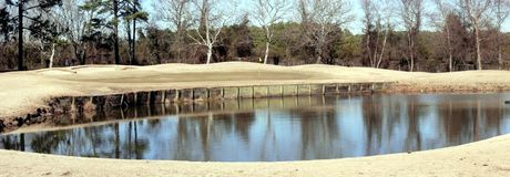 Winter golf hole. Ecologically friendly golf courses will not have green grass during the winter, but the game is just as challenging Royalty Free Stock Photo