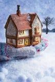 Winter-Häuschen in der behandschuhten Hand Lizenzfreies Stockfoto