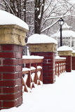 Winter.Handrail of the park bridge. Columns from a brick incorporate to concrete covers a wooden lattice.These are a bridge handrail in park.All is covered by Royalty Free Stock Photo