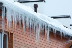 Hanging icicles on the house roof Royalty Free Stock Photo