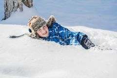 In winter, a happy boy lies on the snow. Stock Photography