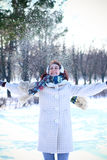 Winter happy girl throwing snow in park outdoors Stock Images