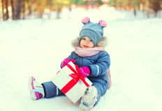Winter happy little child with christmas red box gift on snow Royalty Free Stock Photography