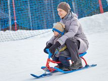 Happy mom with son rides a sled from mountain stock images