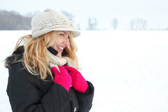 Winter happy woman in snow looking aside or to someone. Copy space outside on cold winter day. Portrait Caucasian smiling female model with pink gloves in Royalty Free Stock Image