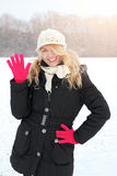Winter happy woman in snow looking up at camera and waving Stock Photos
