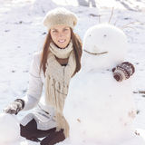 Winter Happy Woman And Snowman. Winter Happy Woman Embracing Snowman in the park. Caucasian female wintertime outdoor Royalty Free Stock Photo