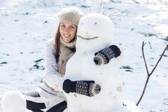 Winter Happy Woman And Snowman. Winter Happy Woman Embracing Snowman in the park. Caucasian female wintertime outdoor Stock Photo