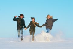 Happy young people running winter outdoors Royalty Free Stock Photo