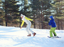 Winter happy young smiling mother with son child go skiing having fun in forest on mountain Stock Images
