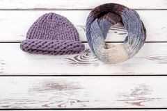 Winter hat and twisted scarf. White wooden desks surface background stock photography