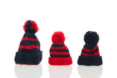 Winter hats. Red and blue knitted winter hats isolated over white background royalty free stock image