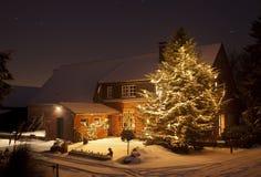 Winter-Haus mit hohem Weihnachtsbaum nachts Lizenzfreie Stockfotos