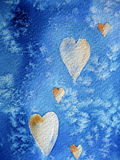 Winter hearts. Photograph of a watercolour painting with hearts and snowflakes on a blue background, created by the photographer herself Stock Photos