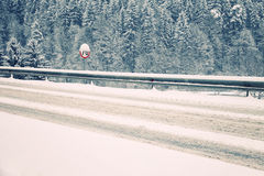 Winter heavy snowy road. Heavy snowy winter street road with speed limit table Royalty Free Stock Photo
