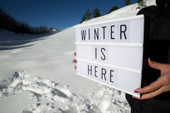 Winter is here. Slogan `winter is here` held by a woman in a snowy landscape Stock Image