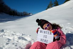 Winter is here. Slogan `winter is here` held by a girl in a snowy landscape Stock Photo