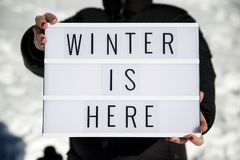 Winter is here. Slogan `winter is here` held by a woman in a snowy landscape Royalty Free Stock Photo