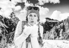 Traveller woman in winter outdoors blowing snow at camera. Winter on higher level of fun. smiling modern traveller woman in the front of mountain scenery in Alto Royalty Free Stock Photos